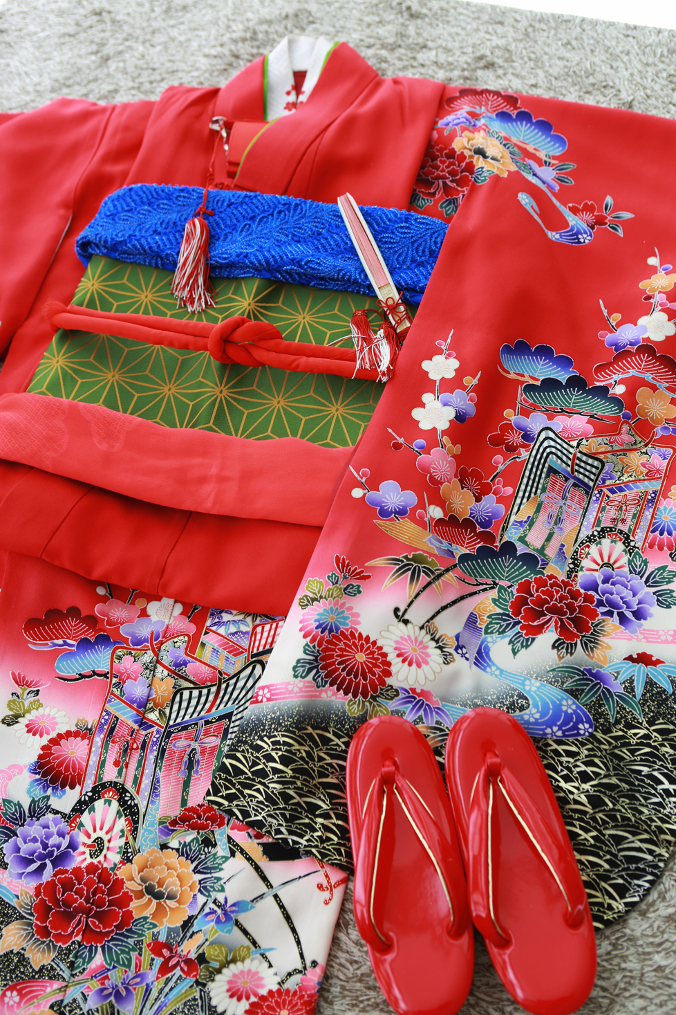 鮮やかな赤い着物。袖と裾には、赤に映える色とりどりの模様がとても素敵です。着物の赤と対象的な帯揚げの青が、鮮やかさを引き立てます。