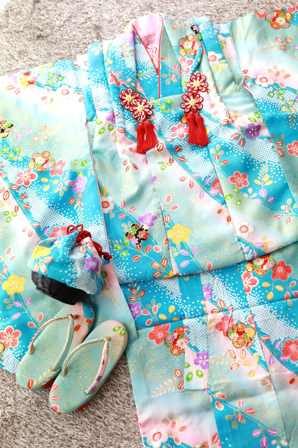 水色地に色とりどりのお花が描かれ、明るい色使いがとても可愛らしい被布セットです。